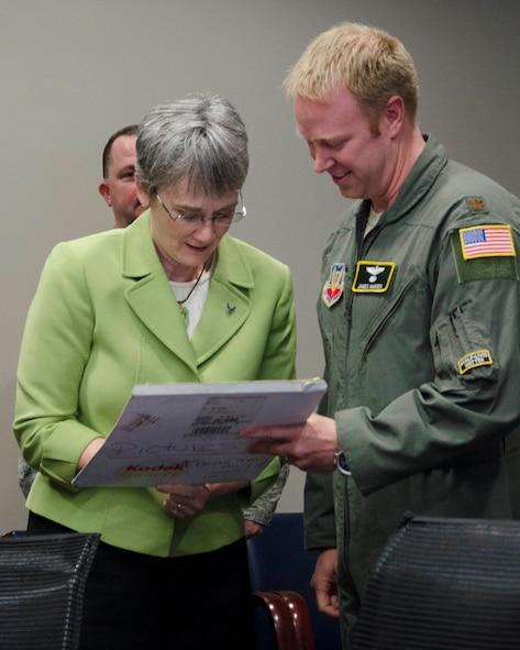 Maj. James A. Hansen II, director of operations, Air Force Technical Applications Center, Patrick AFB, Fla., watches as Secretary of the Air Force Heather Wilson autographs a photo from Hansen's U.S. Air Force Academy graduation ceremony.  Wilson sponsored Hansen when she was a U.S. representative for the state of New Mexico, and was pictured in the photo with Hansen and President George W. Bush.  (U.S. Air Force photo by Susan A. Romano)