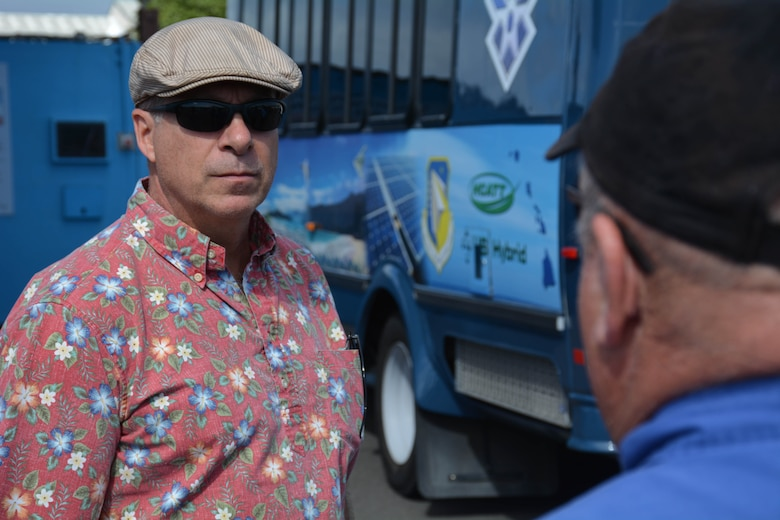Man listens to another man speak in front of a hydrogen-powered bus