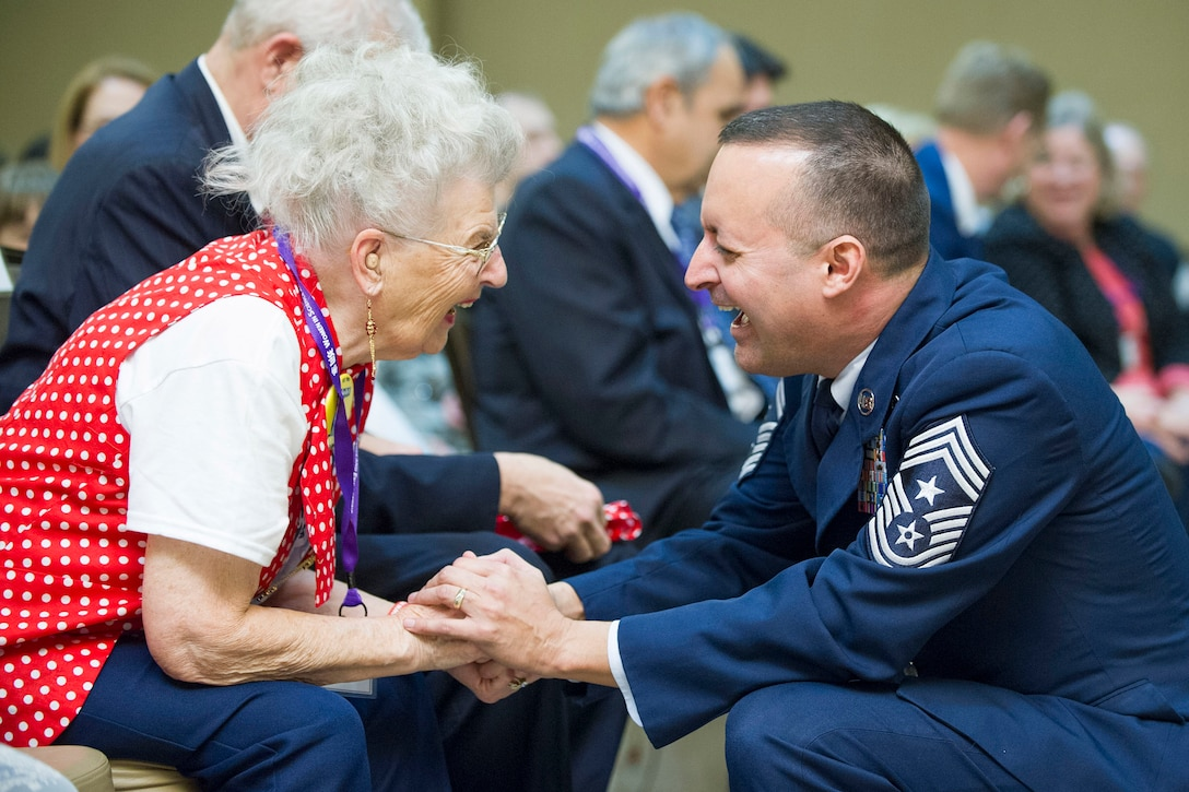 "Chief Master Sgt. Michael Joseph, command chief for the Air Force Technical Applications Center, Patrick AFB, Fla., shares a hearty laugh with Mae Krier, an original member of ""Rosie the Riveters"" during the 2018 Women in Science and Engineering Symposium Feb. 8, 2018.  AFTAC hosted the event and invited Krier and many other high-profile women in government, education and industry to relay their success stories to young minds interested in pursuing careers in science, technology, engineering and math.  (U.S. Air Force photo by Phillip C. Sunkel IV)"