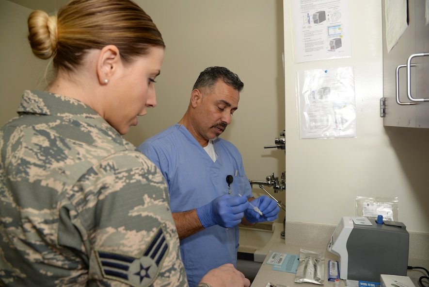 Joe Contreras and Senior Airman Amber Scandridge conduct a practice test of the new Roche LIAT in the Urgent Care Clinic at Wilford Hall on Joint Base San Antonio Lackland Feb. 6, 2018. The new testing system, according to officials in the clinic, improves patient care by reducing the amount of time to determine if a patient has the flu from 48 hours down to less than 30 minutes.