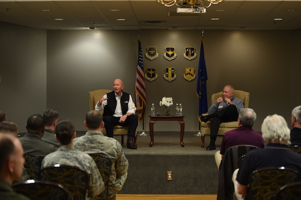 Two retired military men sit on stage.