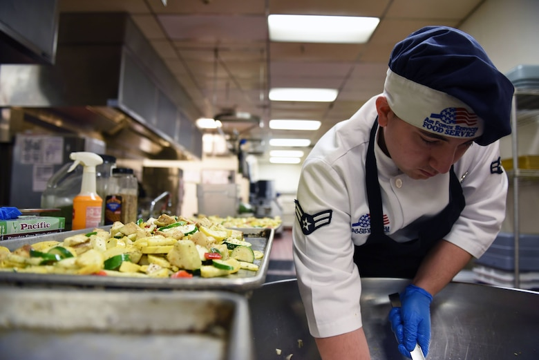Airman 1st Class Zachary Wilson, 60th Force Support Squadron food service technician, scoops vegetables from out of a bowl where they had been tossed in various sauces and seasonings Feb. 11 at Travis Air Force Base, Calif. Wilson joins the Sierra Inn Dining Facility team in representing Travis during the John L. Hennessy competition Feb. 20-23.