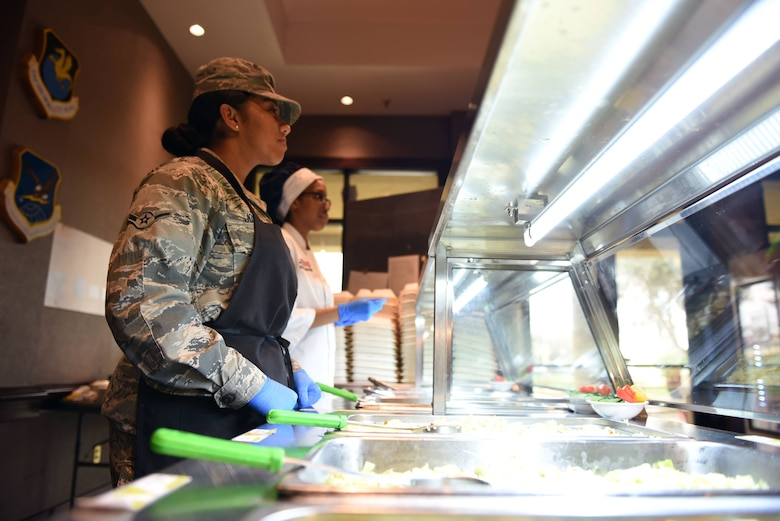 Airman Melanie Moore, 60th Force Support Squadron food service specialist, and Airman Domonique Jordan, 60th FSS food service apprentice, wait on customers at the base Dining Facility Feb. 11 at Travis Air Force Base, Calif. Moore and Jordan join the rest of the Sierra Inn DFAC team in representing Travis at the John L. Hennessy competition Feb. 20-23.