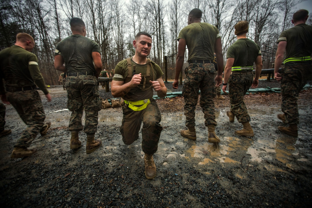 A Marine lunges outside while five others stand behind him facing the reverse direction.