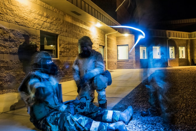 Airmen, illuminated in blue light, gather on a sidewalk outside a building.