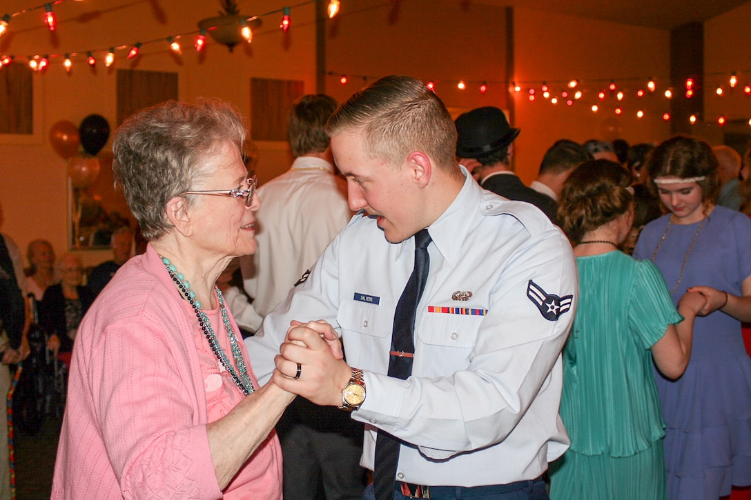 """Airman First Class Austyn Salyers, 75th Air Base Wing Communications and Information Directorate, dances with a resident of Chancellor Gardens Senior Living Center in Clearfield Feb. 13 at the Valentines Dance. More than 60 residents attended and mingled with Team Hill guests. Staff members noted that the Team Hill Airmen are """"always the highlight of the event."""" (U.S. Air Force photo by Jen Eaton)"""