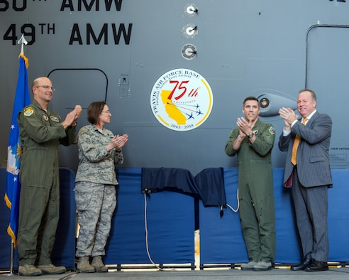 From left, U.S. Air Force Col. Raymond Kozak, 349th Air Mobility Wing commander, Col. Ruth Meyer, 621st Contingency Resonse Wing, Col. John Klein, 60th Air Mobility Wing commander, and State Senator Bill Dodd (D-Napa), 3rd Senate District, reveal the 75th Anniversary logo during a ceremony at Travis Air Force Base, Calif., Feb. 8, 2018. Travis is celebrating 75 years as a major strategic logistics hub for the Pacific and integral part of global power projection for the total force. (U.S. Air Force photo by Louis Briscese)