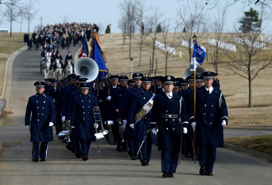 Ceremonial Guardsmen and the Band march toward the gravesite during retired Col. Leo Thorsness's full honors funeral at Arlington National Cemetery, Arlington, Va., Feb. 14, 2018. Thorsness was a Vietnam Prisoner of War and Medal of Honor recipient. (U.S. Air Force photo by Staff Sgt. Rusty Frank)
