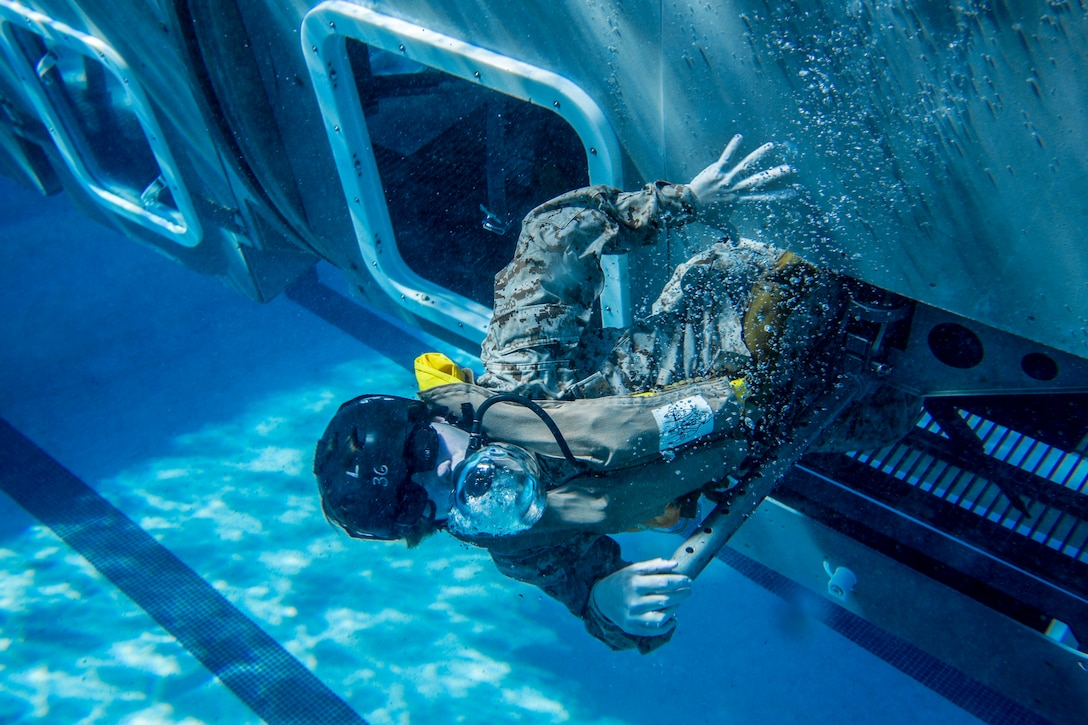 A Marine swims out from an opening in a mock helicopter at the bottom of a swimming pool.