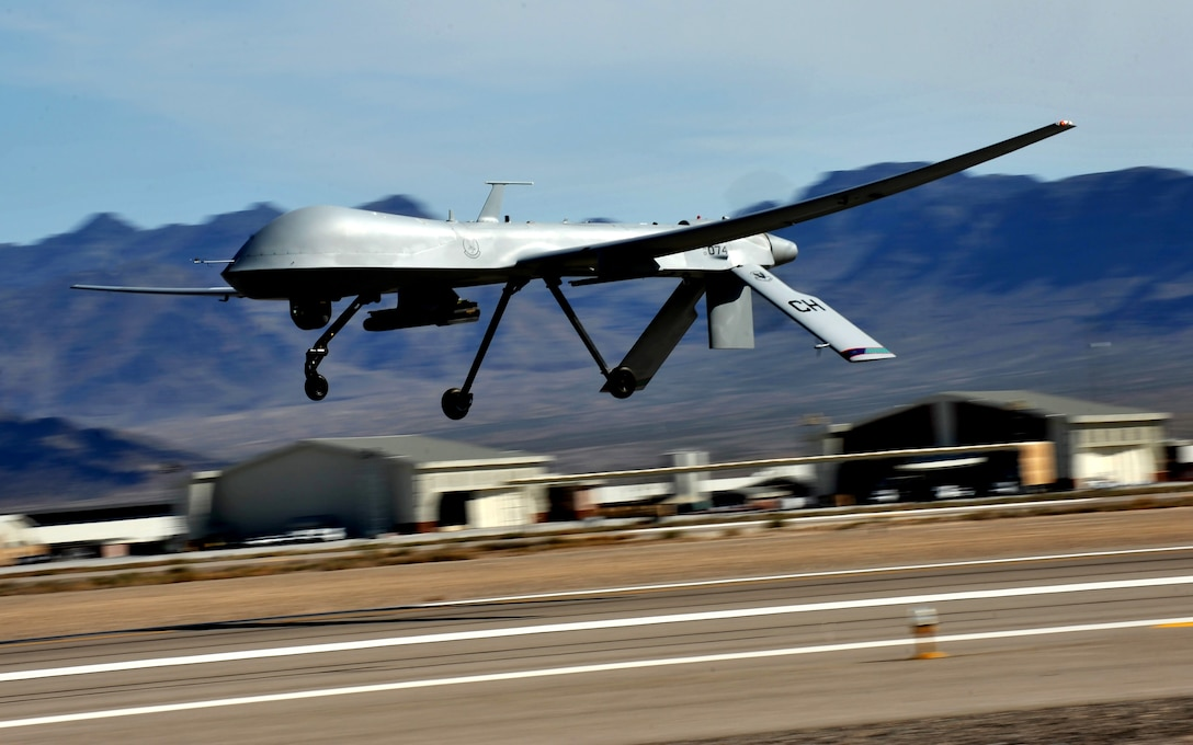 An MQ-1 Predator flies above the flight line during launch and recovery training at Creech Air Force Base, Nevada March 14, 2015. The weaponizing of Predator by Bill Grimes' Big Safari team is credited with changing the way air wars are fought. (U.S. Air Force photo/Senior Master Sgt. Cecilio Ricardo)