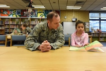 Tech. Sgt. Jere Ross, 86th Airlift Wing noncommissioned officer of resources and requirements, and Airman 1st Class Sarah Marcinko, 569th United States Forces Police Squadron security forces personnel, read with children on Feb. 6, 2018 at Vogelweh Elementary School on Vogelweh Military Complex, Germany. Children select a book based on their reading ability and then read to their military volunteer for up to 30 minutes at a time.