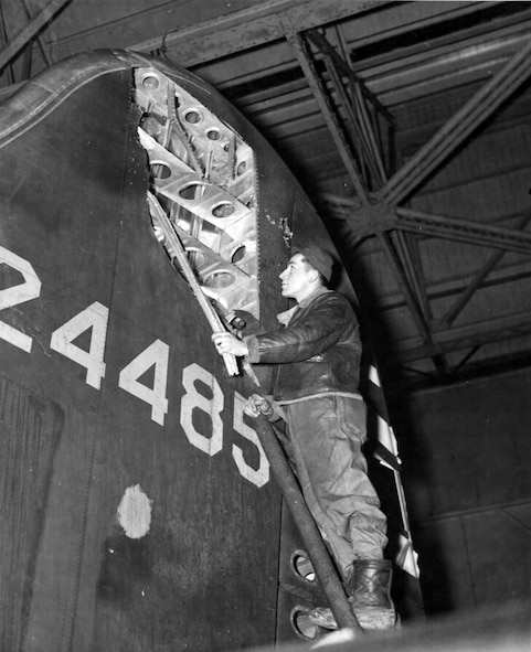 The Boeing B-17F Memphis Belle tail is inspected for damage after a mission on January 23, 1943. (U.S. Air Force photo)