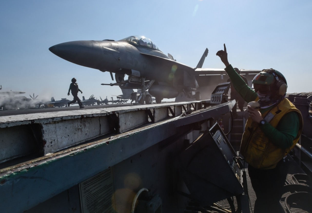 An aircraft prepares to launch on the USS Theodore Roosevelt's flight deck.