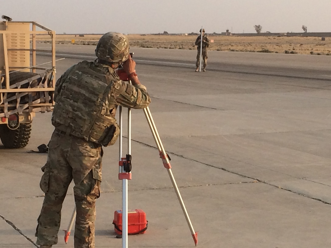 TSgt Ruben Hernandez (forefront) and Capt Miles Ryan (background) are surveying the extent of a depression in a runway in Qayyarah-West, Iraq.