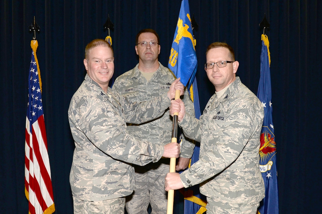 Col. James DeVere, 302nd Airlift Wing commander, passes the 302nd Maintenance Group guidon to the new group commander, Col. Jason Martin, at an assumption of command ceremony, Feb. 11, 2018, at Peterson Air Force Base, Colorado.