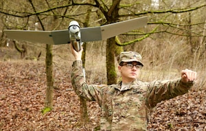 Soldier prepares to launch small drone.