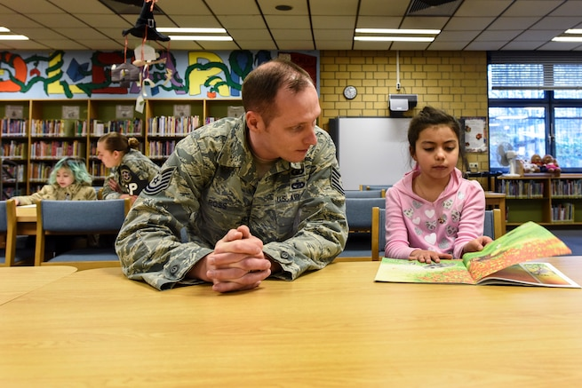 Two airmen listen as children read to them in a school library.