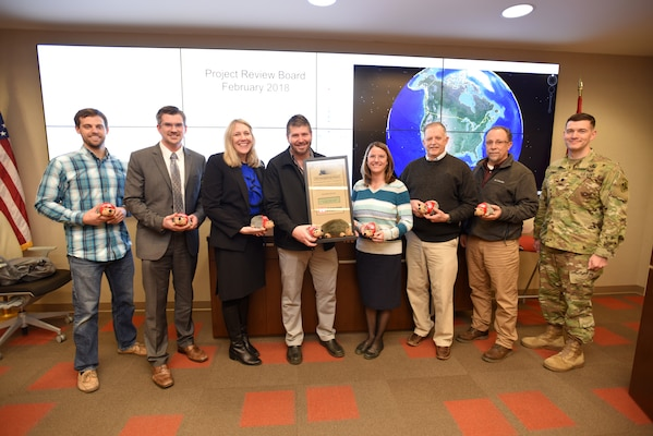Lt. Col. Cullen Jones (Right), U.S. Army Corps of Engineers Nashville District commander, presents the Hedgehog Award to a team credited with ensuring a construction project for the U.S. Department of Energy at Oak Ridge, Tenn., finished on time and $5 million under budget. The award is given quarterly by the Nashville District to individuals or team of employees to recognize excellence at the district's headquarters in Nashville, Tenn. Those present at the presentation are (Left to Right) Barry Cunningham, Isaac Taylor, Bonnie Jagoditz, Jason Phillips, Jacqueline Huff, Joe Duncan, Brian Whitus, and Jones. (USACE photo by Lee Roberts)