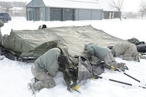 Wisconsin National Guard Airmen assigned to the 115th Fighter Wing Joint Interoperability Site Communications Capability team work together in freezing temperatures to establish a temporary operating site for the State Interoperable Mobile Communications Exercise (SIMCOM), in Fitchburg, Wis., Feb 7, 2018. The annual SIMCOM exercise tests the interoperability of federal, state and local emergency communications agencies. (U.S. Air National Guard photo by Tech. Sgt. Mary Greenwood)