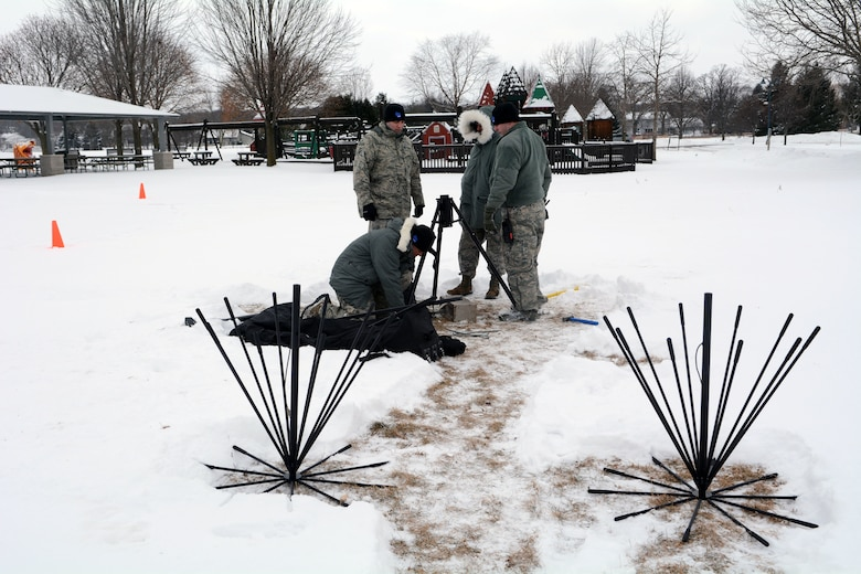 Airmen assigned to the 115th Fighter Wing Joint Interoperability Site Communications Capability package work together to erect a multiband antenna mast for the State Interoperable Mobile Communications Exercise (SIMCOM), in Fitchburg, Wis., Feb 7, 2018. The annual SIMCOM exercise tests the interoperability of federal, state and local emergency communications agencies. (U.S. Air National Guard photo by Tech. Sgt. Mary Greenwood)