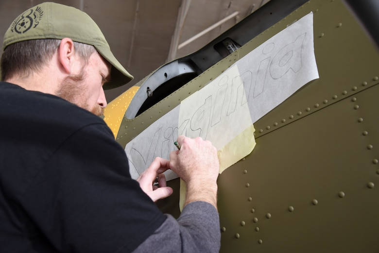 (01/25/2018) -- Museum restoration specialist Chad Vanhook paints the name 'Virginia' below the right waist gun position of the Boeing B-17F Memphis Belle as part of the aircraft restoration. (U.S. Air Force photo by Ken LaRock)