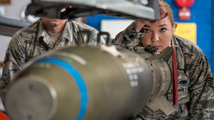 An airman watches as crews move an MK-82 into place.