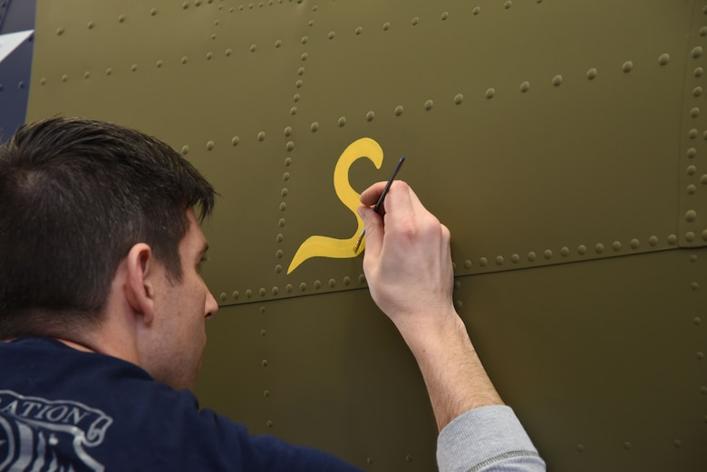 (01/25/2018) Museum restoration specialist Casey Simmons paints the letter 'S' for 'Sally' below the left waist gun position of the Boeing B-17F Memphis Belle as part of the aircraft restoration. Plans call for the aircraft to be placed on permanent public display in the WWII Gallery of the National Museum of the U.S. Air Force on May 17, 2018. (U.S. Air Force photo by Ken LaRock)