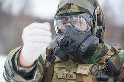 Senior Airman Michael Carlson, assigned to the 673d Civil Engineer Squadron, Explosives Ordinance Disposal Flight, quickly dons protective gear before a live-fire demolitions exercise in Mission Oriented Protective Posture 4 on Joint Base Elmendorf-Richardson, Alaska, Feb.14, 2018.  The Airmen were conducting EOD training in a simulated chemical weapons contaminated environment.