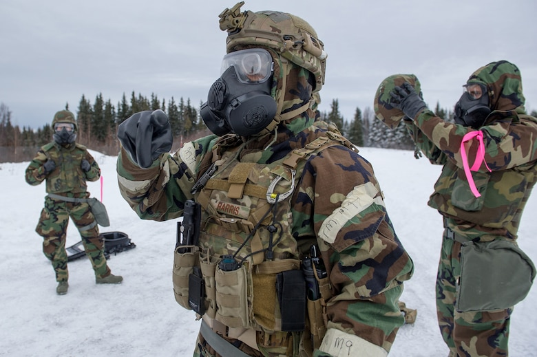 Air Force Staff Sgt. Joshua Harris, assigned to the 673d Civil Engineer Squadron, Explosives Ordinance Disposal Flight, gives instruction to fellow Airmen as they don protective gear before a live-fire demolitions exercise in Mission Oriented Protective Posture 4 on Joint Base Elmendorf-Richardson, Alaska, Feb.14, 2018.  The Airmen were conducting EOD training in a simulated chemical weapons contaminated environment.