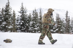 An Airman assigned to the 673d Civil Engineer Squadron, Explosives Ordinance Disposal Flight, walks on a live-fire demolitions range in Mission Oriented Protective Posture 4 on Joint Base Elmendorf-Richardson, Alaska, Feb.14, 2018.  The Airmen were conducting EOD training in a simulated chemical weapons contaminated environment.