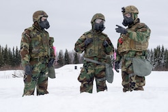 Airmen assigned to the 673d Civil Engineer Squadron, Explosives Ordinance Disposal Flight, observe preparations for a live-fire demolitions exercise in Mission Oriented Protective Posture 4 on Joint Base Elmendorf-Richardson, Alaska, Feb.14, 2018.  The Airmen were conducting EOD training in a simulated chemical weapons contaminated environment.