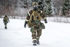 Senior Airman Michael Carlson, assigned to the 673d Civil Engineer Squadron, Explosives Ordinance Disposal Flight, walks of the range prior to conducting a live-fire demolitions exercise in Mission Oriented Protective Posture 4 on Joint Base Elmendorf-Richardson, Alaska, Feb.14, 2018.  The Airmen were conducting EOD training in a simulated chemical weapons contaminated environment.