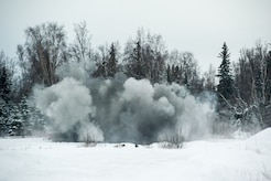 Explosive charges detonate throwing snow and debris into the air as Airmen assigned to the 673d Civil Engineer Squadron, Explosives Ordinance Disposal Flight, conduct a live-fire demolitions exercise in Mission Oriented Protective Posture 4 on Joint Base Elmendorf-Richardson, Alaska, Feb.14, 2018.  The Airmen were conducting EOD training in a simulated chemical weapons contaminated environment.