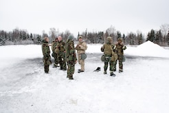 Airmen assigned to the 673d Civil Engineer Squadron, Explosives Ordinance Disposal Flight, stand near the blast area after a live-fire demolitions exercise in Mission Oriented Protective Posture 4 on Joint Base Elmendorf-Richardson, Alaska, Feb.14, 2018.  The Airmen were conducting EOD training in a simulated chemical weapons contaminated environment.