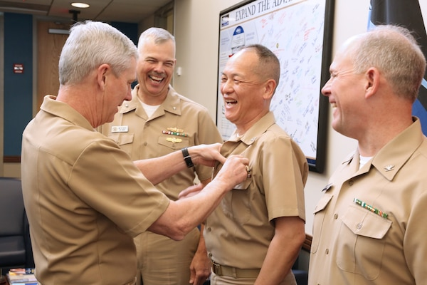 Vice Adm. Tom Moore pins Capt. Huan Nguyen, deputy chief information officer, NAVSEA;  with an Engineering Duty Officer (EDO) qualification insignia as recently pinned Rear Adm. Ronald Fritzemeier, Space and Naval Warfare Systems Command (SPAWAR) chief engineer;  and soon to be pinned Capt. Mark Mclean, principal acquisition program manager with Acquisition and Finance, Program Executive Office Littoral Combat Ships.