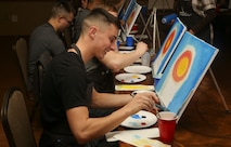 """Marines paint a picture during a """"Singles Painting Party"""" aboard Marine Corps Air Station Beaufort, Feb. 14. The Marines were recreating a painting of the flag raising during the Battle of Iwo Jima. The party was led by Wine and Design, a company that offers step by step help to encourage others to create their own piece of art."""