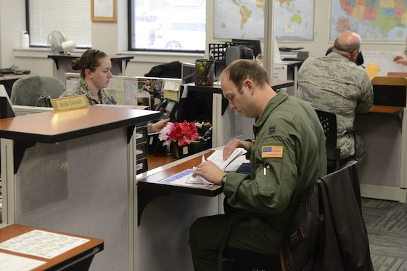 One female airman sits at a desk across from a male airman in a flight suit looking through a folder of paperwork.