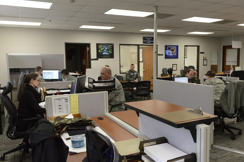 A large office is filled with desks and people working at those desks.