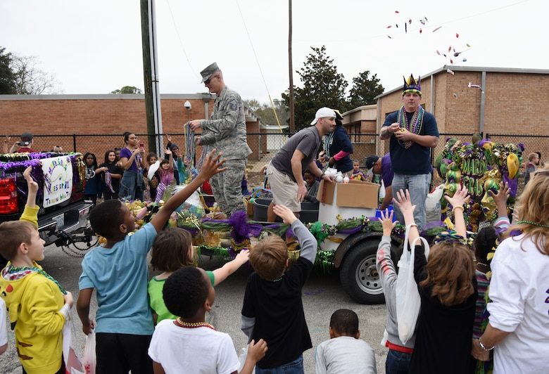 Keesler personnel toss candy and beads to children during the Jeff Davis Elementary School Mardi Gras parade Feb. 9, 2018, in Biloxi, Mississippi. Keesler leadership and other base personnel also participated in the festivities. (U.S. Air Force photo by Kemberly Groue)
