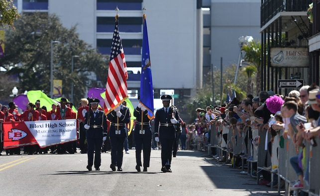 Members of the Keesler Air Force Base Honor Guard lead the Gulf Coast Carnival Association Mardi Gras parade Feb. 13, 2018, in Biloxi, Mississippi. Keesler personnel participate in local parades every Mardi Gras season to show their support of the communities surrounding the installation. (U.S. Air Force photo by Kemberly Groue)