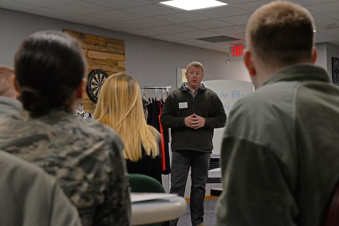 Chief Master Sgt. Adam Vizi, the 28th Bomb Wing command chief, briefs a group of Airmen and their spouses on appropriate attire during the first spouse's orientation program in the Samuel O. Turner building at Ellsworth Air Force Base, S.D., Jan. 12, 2018. During the course, attendees learned about the appropriate attire for formal military events, the importance of creating networks and proper military etiquette. (U.S. Air Force photo by Airman 1st Class Nicolas Z. Erwin)