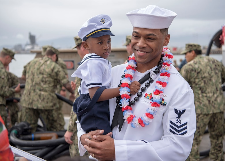 USS Texas (SSN 775) and native of Chicago, Illinois, holds his son on the submarine pier in Joint Base Pearl Harbor-Hickam, Feb. 14.