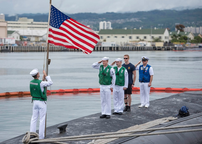 USS Texas (SSN 775) render honors to the national ensign following the completion of a Western Pacific deployment in support of national security, Feb. 14.