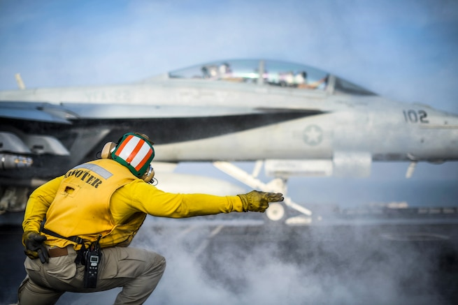 A sailor extends his arm to signal to an aircraft to launch from a ship's deck.