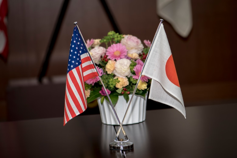 "U.S. and Japan protocol flags sit next to a bundle of flowers on a table during a meeting between U.S. Air Force Master Sgt. Cesar Ventura and two Japan Air Self-Defense Force warrant officers with the 3rd Air Wing at Misawa Air Base, Japan, Feb. 14, 2018. The three met to discuss one of the warrant's retirement plans. This meeting reflects a very common theme for the three men who over the past four years have become ""like family."" Ventura is a vertical inspections planner with the 35th Fighter Wing's Inspector General's office and hails from Los Angeles, California. (U.S. Air Force photo by Tech. Sgt. Benjamin W. Stratton)"