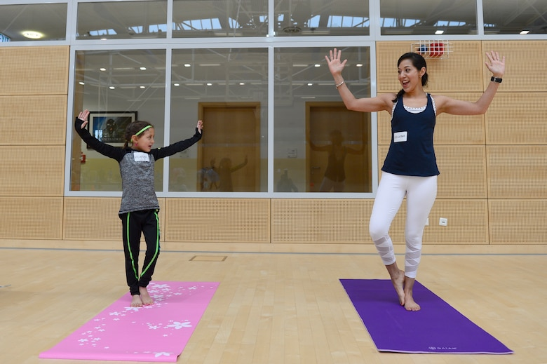 Capt. Laura Pfledderer, 52nd Medical Operations Squadron social worker, and her daughter Isabella, showcase their yoga skills during Fit Family Fun Day at the PowerHaus Fitness Center at Spangdahlem Air Base, Germany, Feb. 10, 2018. Pfledderer and her daughter led a beginner's yoga class during the event to teach various relaxation techniques. (U.S. Air Force photo by Airman 1st Class Jovante Johnson)