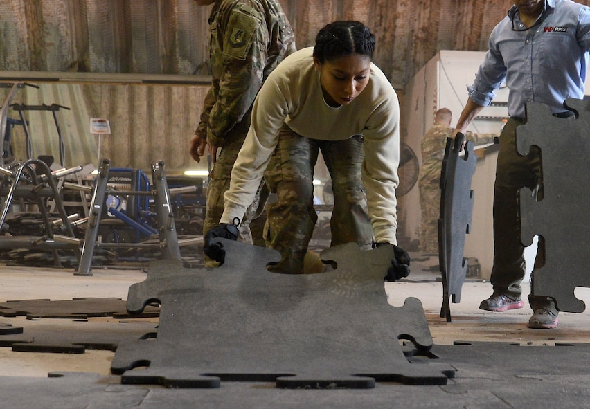 Senior Airman Astrid Hernandez, 455th Expeditionary Force Support Squadron contracting officer representative, lays flooring in the Warrior Fitness Center Feb. 10, 2018 at Bagram Airfield, Afghanistan.