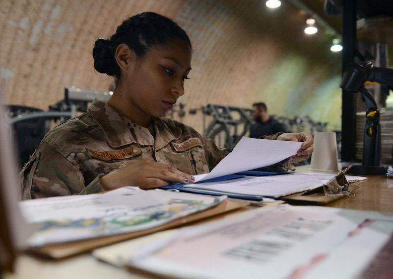 Senior Airman Astrid Hernandez, 455th Expeditionary Force Support Squadron contracting officer representative, looks over her checklist in The Rock fitness center Feb. 13, 2018 at Bagram Airfield, Afghanistan.
