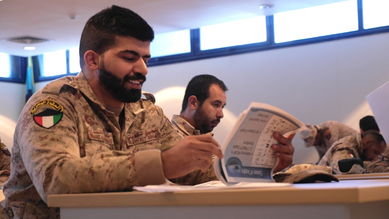 Lance Cpl. Ahmed Saed Al Shamari, a member of the Kuwaiti Marine Battalion, reviews an information packet passed out by Marines from the Command Element and Logistics Combat Element, Special Purpose Marine Air-Ground Task Force – Crisis Response – Central Command during a Tactical Resupply Subject Matter Expert Exchange at the Kuwait Naval Institute. Exchanging logistic concepts and best practices allowed participants to learn from each other and strengthened relationships.