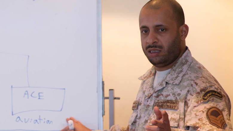 Kuwaiti Marine First Sgt. Bader M. Al-Hubaiter, an infantryman with the Kuwaiti Marine Battalion, explains the battalion's organization to U.S. Marines with the Command Element and Logistics Combat Element, Special Purpose Marine Air-Ground Task Force – Crisis Response – Central Command during a Tactical Resupply Subject Matter Expert Exchange held at the Kuwait Naval Institute. Participants exchanged logistic concepts and best practices to learn from each other and strengthen relationships. Bader was recognized as one of the outstanding attendees of the course and received a command coin in recognition following the training.